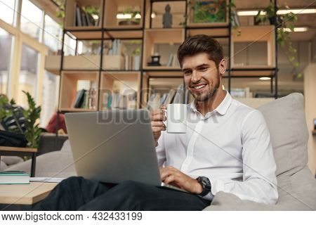 Young smiling european businessman drinking tea or coffee from cup and using laptop computer. Concept of modern successful man. Bearded stylish guy wearing formal clothes. Office interior. Daytime