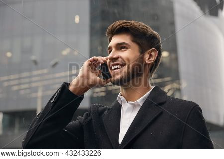Young smiling european businessman talking on mobile phone in city. Concept of remote work. Modern successful man. Bearded stylish guy wearing coat. Rainy daytime