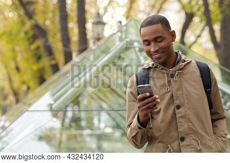 Smiling black male student standing and using mobile phone. Young african man wear parka coat and backpack. Blurred glass building in city on background. Autumn daytime