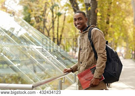 Smiling black male student standing and holding notebook paper. Young african man wear parka coat and backpack. Person looking at camera. Blurred glass building in city on background. Autumn daytime