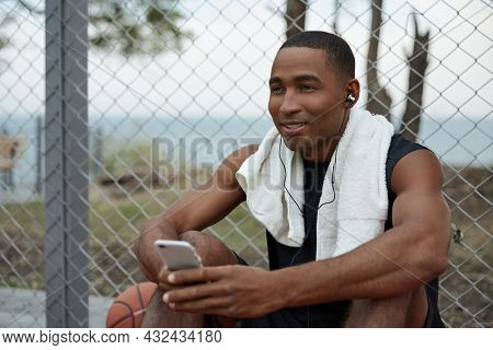 Young african sportsman listening music in headphones on mobile phone. Black man with towel wear sportswear. Urban basketball player. Daytime