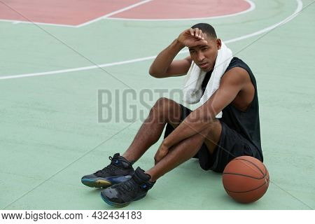 Young tired african sportsman sitting on sports court with basketball ball and wiping forehead after training. Black man with towel wear sportswear and sneakers. Urban basketball player. Daytime