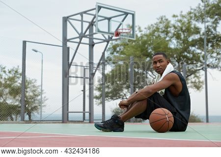 Young focused african sportsman sitting on sports court with basketball ball and looking somewhere. Black man with towel wear sportswear and sneakers. Urban basketball player. Cloudy day