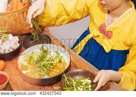 Young Korean Women In Golden Hanbok Cook Traditional Kimchi Dishes Using Fresh And Quality Ingredien
