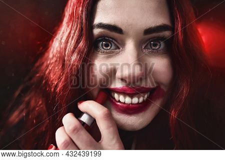 Halloween Time. Portrait Of Crazy-looking Horror Woman With Red Hair She Is Smearing Red Lipstick On
