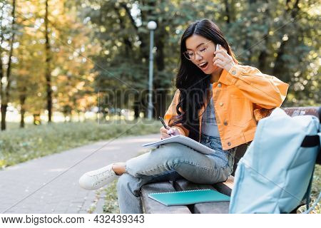 Astonished Asian Woman Writing In Notebook While Talking On Smartphone On Bench In Park