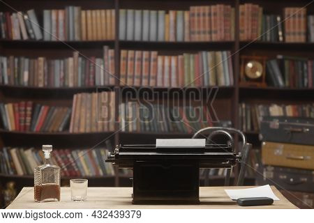 Close-up Of The Writer\'s Workplace, Desk. On The Table There Is A Bottle Of Alcohol And A Vintage T