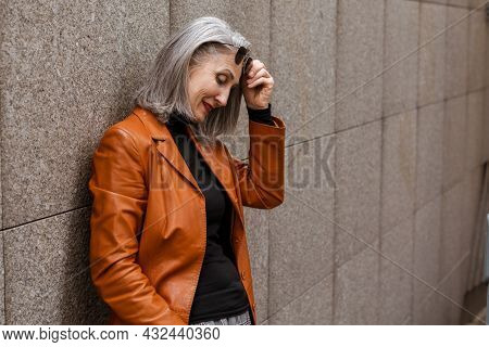 Grey senior woman in leather jacket smiling while leaning on wall outdoors