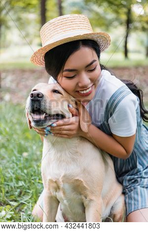 Young And Happy Asian Woman Cuddling Yellow Labrador In Park