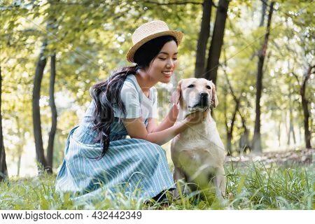 Young Asian Woman In Straw Hat Cuddling Yellow Labrador In Park