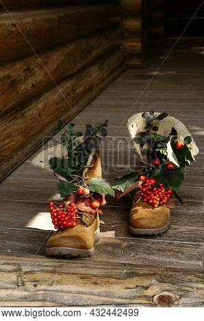 Tracking Boots With Autumn Berries And Leaves Walking On The Porch Of A Wooden Country House.
