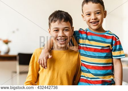 Two smiling preteen african boys brothers standing hugging at home looking at camera