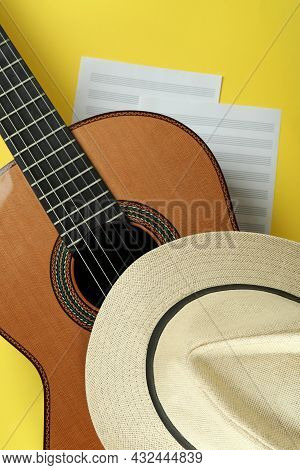 Classical Guitar, Music Sheets And Hat On Yellow Background