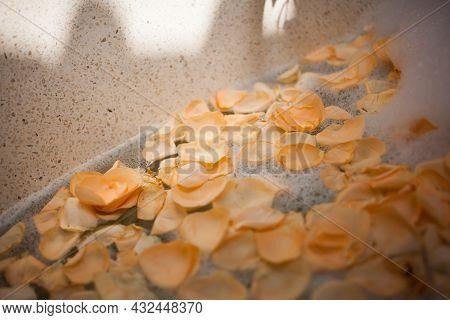 Orange Rose Petals In Bath Tub On Soapy Water