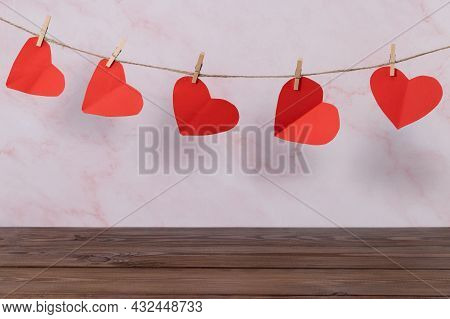 Valentines Day Concept. Empty Wooden Deck Table Over  Wall Background With Heart Shape Garland.