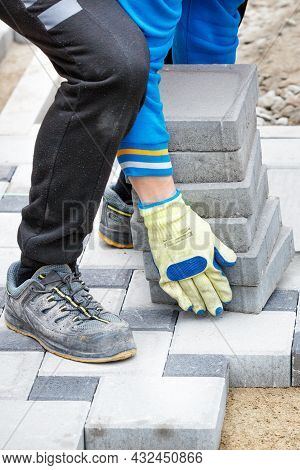 The Hands Of A Worker In Protective Gloves Carry A Stack Of Paving Slabs At The Workplace Along The
