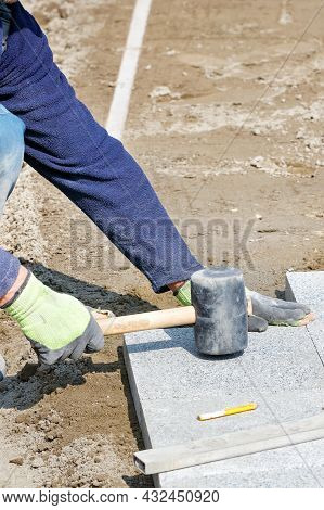 A Worker On A Sunny Day Flattens Granite Tiles With A Rubber Mallet While Assembling A New Sidewalk