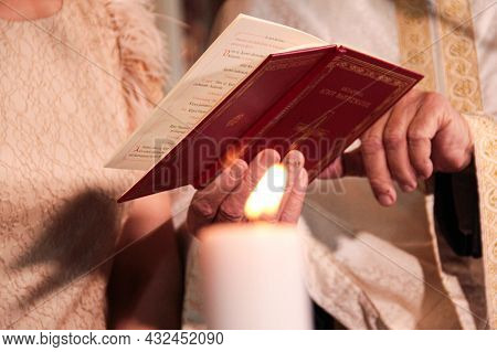 Greek Orthodox Prayer Book And Candle At Baptism