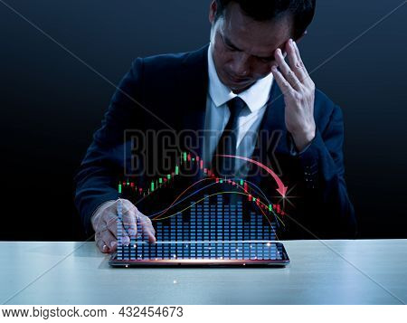 Asian Man In A Suit Sits At His Desk, Left Hand On His Head, He Made Sad Face.right Hand Placed On T