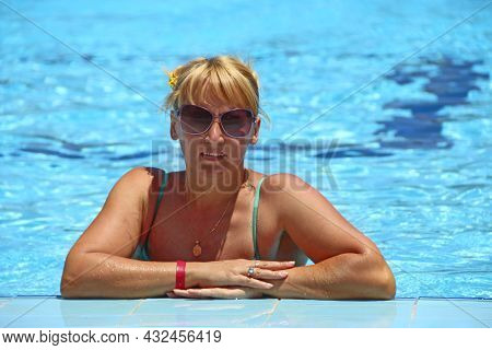 Attractive Woman Posing During Relaxing In Swimming Pool During Vacation. Happy Girl. Young Woman En