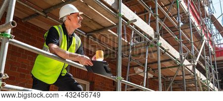 Panorama of man or male builder foreman, construction worker or architect on site holding a clipboard and drinking a mug of coffee or tea panoramic web banner