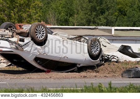 A Traffic Accident On The Road. The Passenger Car Has Turned Over And Is Lying On The Roof After Tur