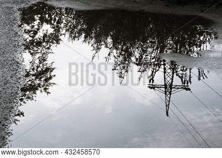 Reflection Of Tall Grass, Power Lines And The Sky With White Clouds In A Large Puddle On The Asphalt