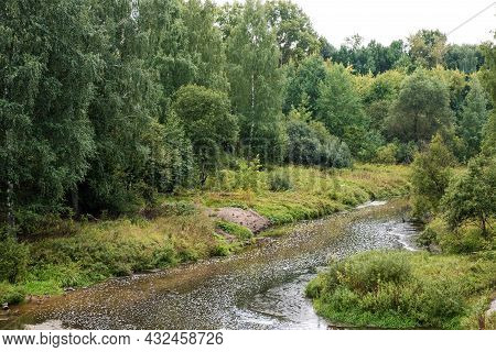 A Small River Among A Dense Green Forest On A Summer Day, Russia.