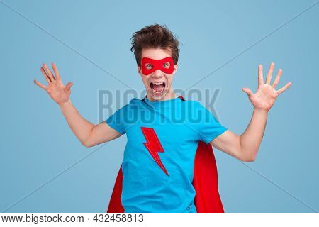Funny Young Guy In Mask And T Shirt With Lightning Bolt Gesticulating And Yelling At Camera While Pr