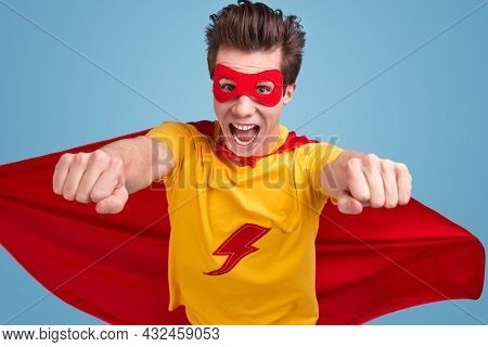 Courageous Young Male In Bright Superhero Costume With Mask And Flying Cape Outstretching Arms And L