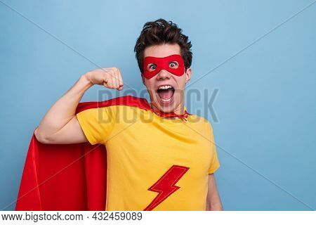 Delighted Young Guy In Superhero Mask And Cape Looking At Camera With Opened Mouth And Demonstrating