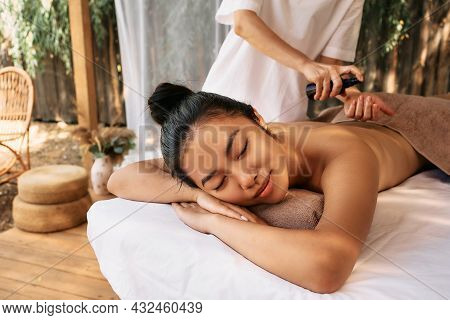 Masseur Applies Aroma Oil To Body Of Asian Young Woman During Massage And Aromatherapy In Beautiful