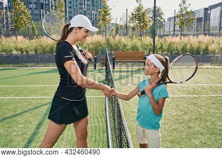 Learning Children Tennis. Female Tennis Player Giving Handshakes To Child Rival Near Tennis Net Befo