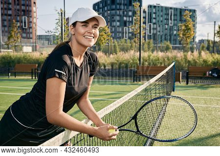 Portrait Of Smiling Female Tennis Player With Tennis Racket Near Net On City Tennis Court