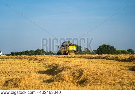 Yellow Combine Harvester New Holland Harvests Ripe Wheat Field. Agriculture In France. Harvesting Is