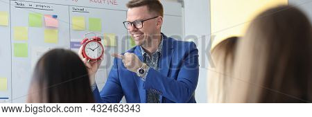 Successful Businessman Speaking At Conference And Showing Time On Red Alarm Clock