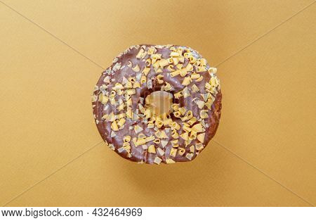 Fresh Chocolate Donut Isolated On Coffee Background. Delicious Dessert With Glossy Chocolate Glaze.