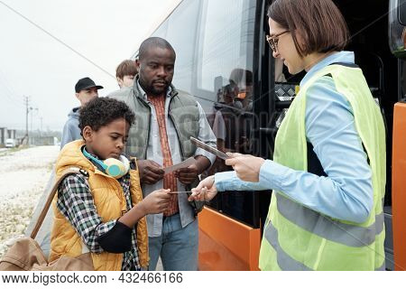 Serious African American father and son showing ticket to transportation supervisor while getting on bus