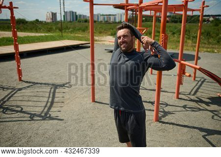 Handsome Mature Sportsman Stretching Arms Behind His Back Before Training On The Sportsground In Ope