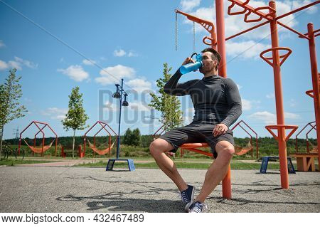 Middle-aged Athlete, Caucasian Sportsman Drinks Water From A Bottle, Resting After Training Outdoors