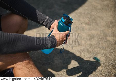 Close-up Of Male Athlete Hands Holding A Blue Bottle Full Of Fresh Water For Rehydrating After Heavy