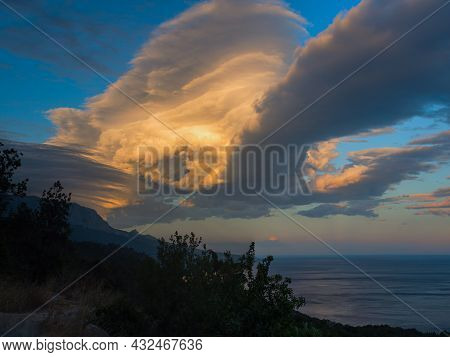 A Thundercloud In The Orange-beige Sunset Light. Dramatic Stormy Sky. A Huge Cumulus Cloud In The Fo
