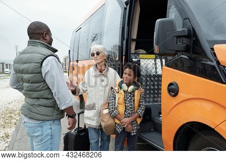 African American man in vest putting grandma and son on bus and listening to grandmothers promise