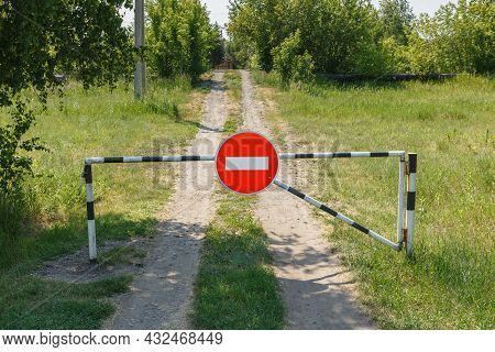 Closed Barrier And Prohibition Sign On A Rural Road. No Entry.