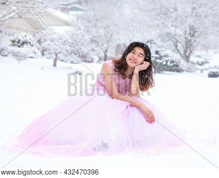 Biracial Teen Girl In Long Formal Pink Gown Sitting Outdoors In Beautiful Snowfall
