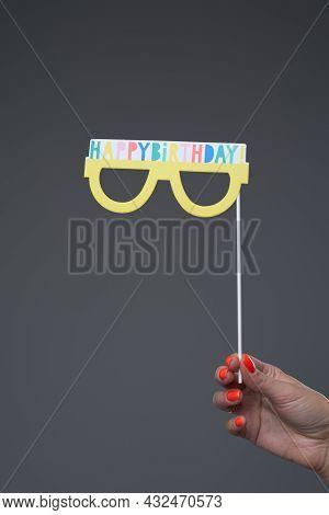 Female Hand Holding Eyewear On Stick With Congratulatory Text