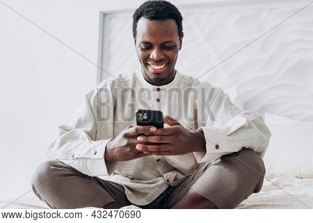 Smiling Young Black Man Waves Hand At Videocall On Smartphone Sitting On Comfortable Bed In Light Ro