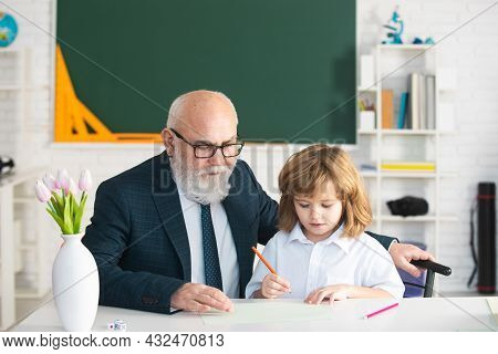 Pupil Reading And Writing With Teacher In Classroom. Old Teacher And Young Schoolboy. Private Lesson
