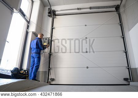 Garage Door Installation And Repair At Home. Contractor Man In House