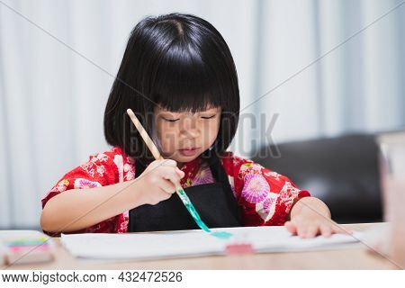 Happy Little Asian Girl Painting With Paintbrush And Watercolor Paints On The Big Paper Art Homescho